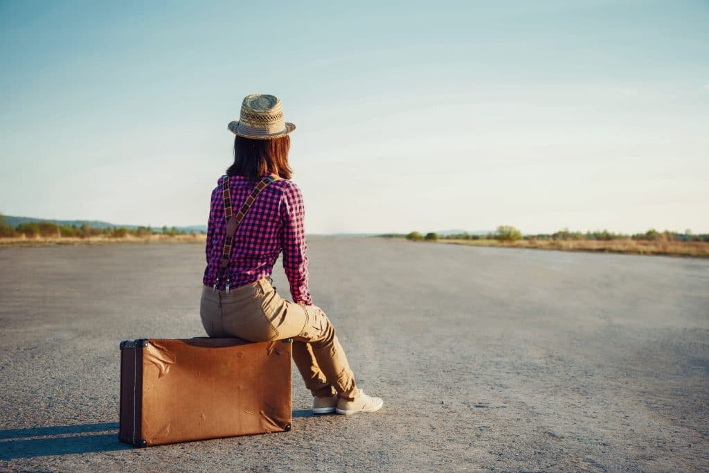 Woman with luggage waiting on the road